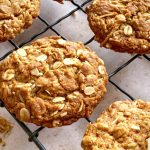 A close up of the Chewy Anzac Biscuits resting on a vintage black wire cooling rack.