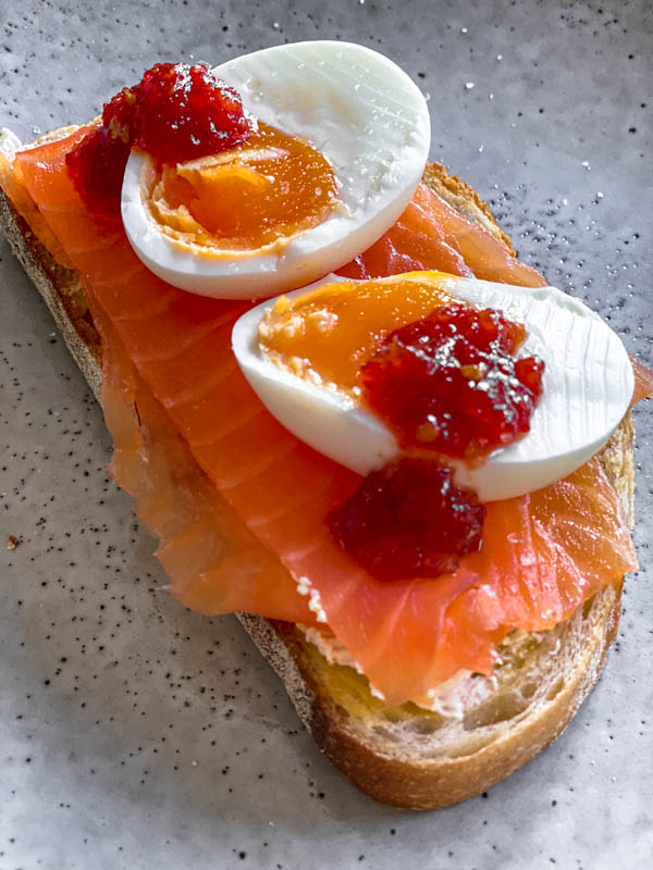 A piece of toast with smoked salmon and boiled eggs that have had some Tomato Chilli Jam dolloped on top. Delicious!