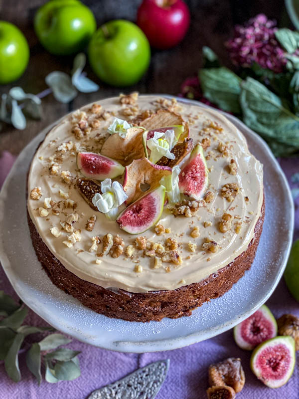 A side on view of the decorated Apple Fig and Walnut Cake with Maple Cream Cheese Frosting.