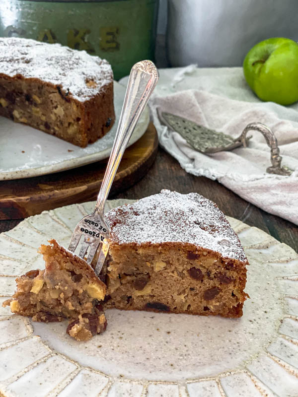 There is a slice of apple cake in the foreground with a cake fork standing up beside it and a piece of cake removed. In the background there is the rest of the cake off to one side, a vintage cake server on top of a napkin and a green apple in the background.