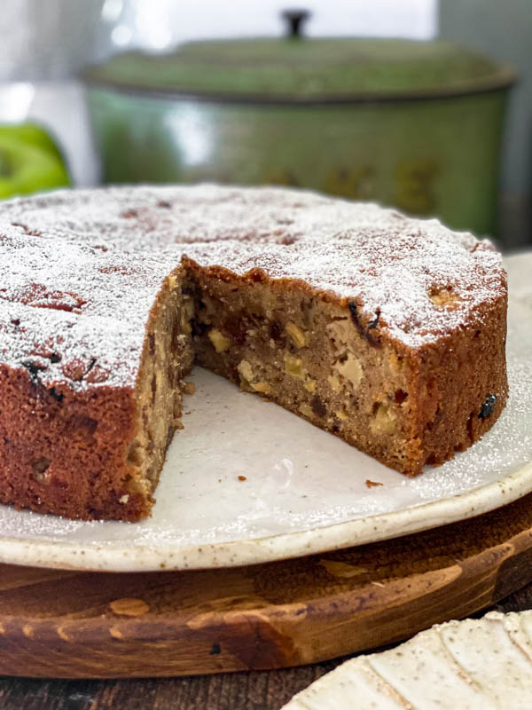 A close up of the inside of the spiced apple cake showing how moist the crumb is and how it is filled with apple and sultanas.