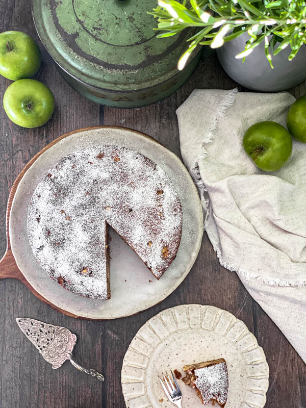 Looking down onto the apple cake that has had a slice removed. There is also a piece of eaten cake on a small plate, a vintage cake server, green apples, a napkin and cake tin on the wooden table as well.