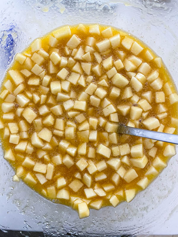 The diced apple is added to the bowl along with the melted butter and sugars.