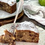 A slice of apple cake on a plate with a silver cake fork on the plate as well.
