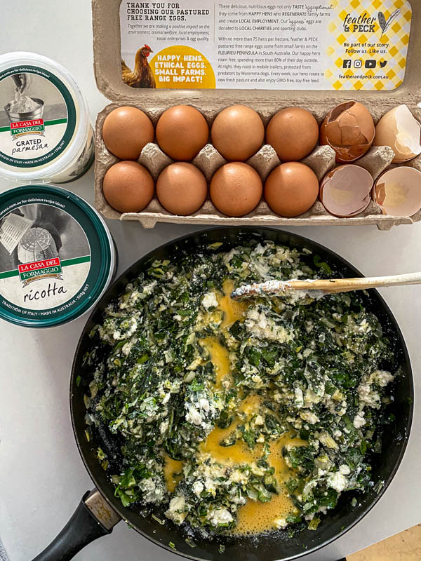 The beaten eggs are now added to the filling. In the background are eggs and cheese containers.