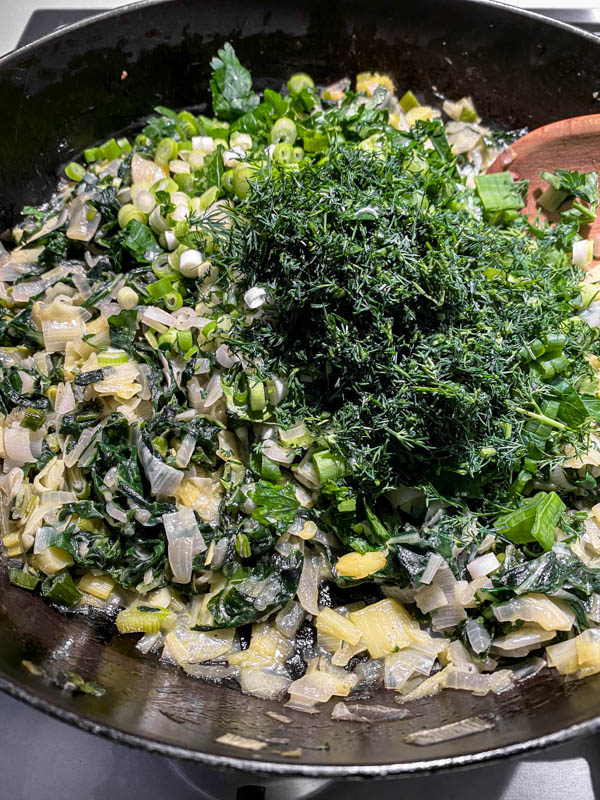 The herbs and spring onions are now added to the silverbeet mixture in the frying pan off the heat.