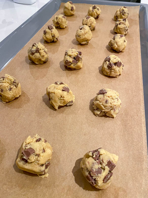 The balls of cookie dough are on an oven tray lined with baking paper. They are shaped into rough balls, not rolled.
