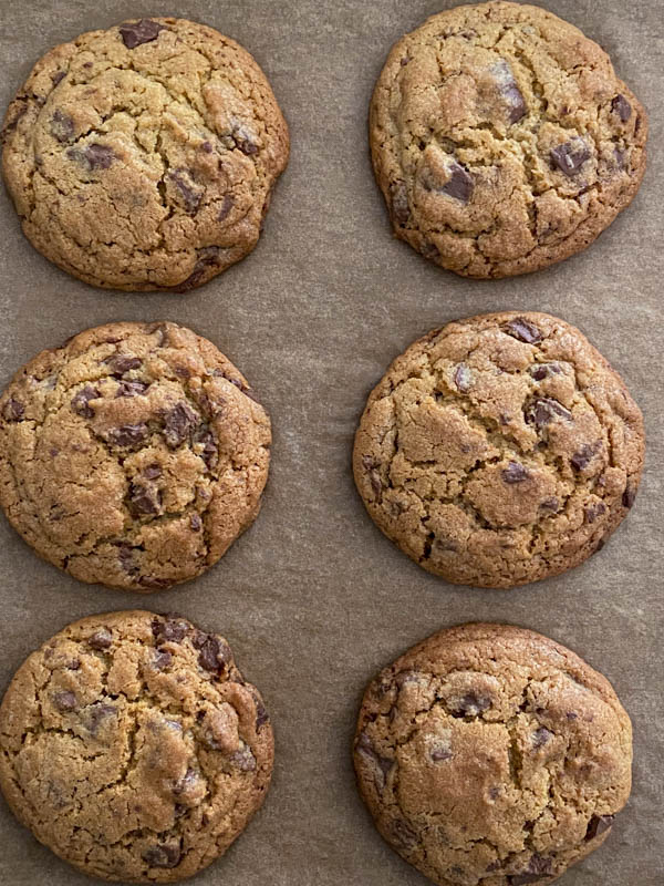 Looking down onto 6 chocolate chip cookies resting on the oven tray.