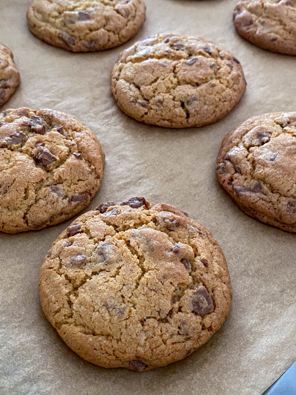 The Chocolate Chip Cookies are cooked and resting on the oven tray until completely cooled.