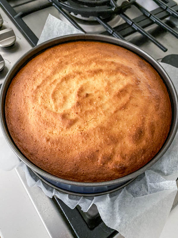 The baked cake is golden brown on top and resting/cooling in the cake tin.