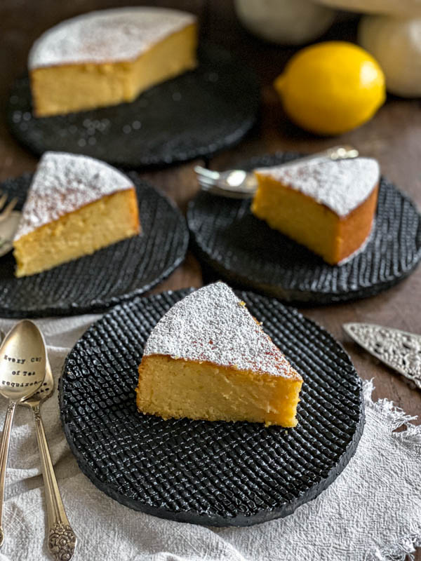 Slices of cake are on black serving plates. The cake is dusted liberally with icing sugar.