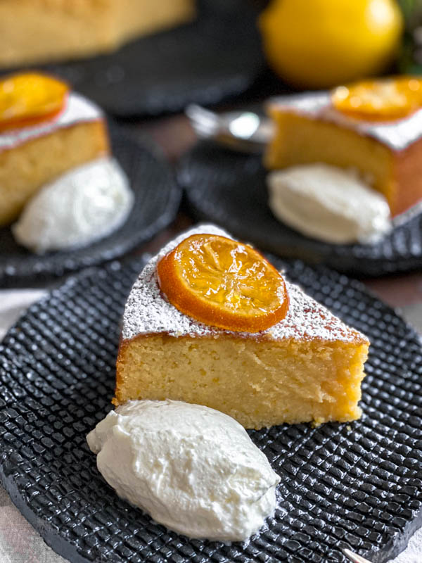 A close up of a slice of Whole Meyer Lemon Cake that has been dusted with icing sugar and also has a slice of confit lemon sitting on top of it. It is served with a dollop of Greek Yoghurt.