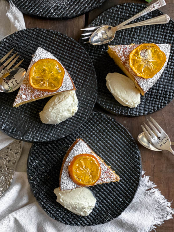 Looking down onto 3 slices of lemon cake. Each slice is topped with a confit lemon slice and has been dusted with icing sugar. They also have a dollop of yoghurt beside each cake slice.