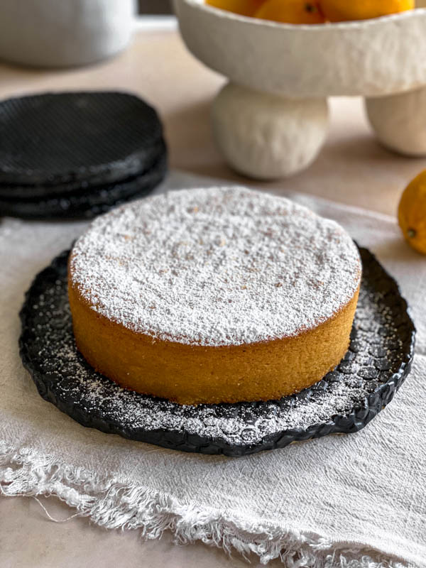 The Whole Meyer Lemon Cake is liberally dusted with icing sugar and is on a black ceramic serving plate on a table with a piece of cloth underneath the plate.