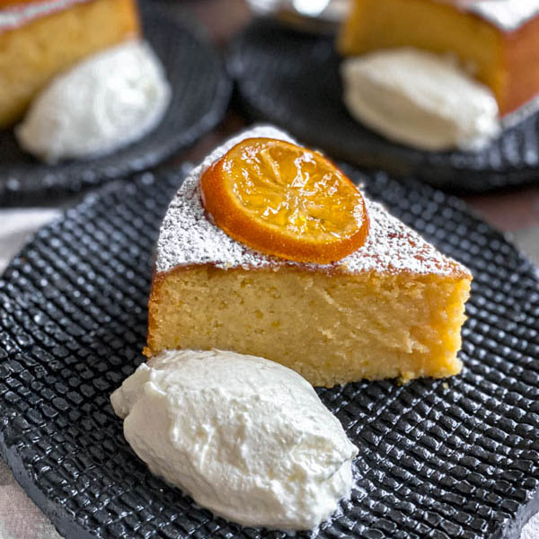 A close up of a slice of the lemon cake on a black textured plate. It is served with a dollop of yoghurt and a slice of confit lemon.