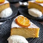 A piece of lemon cake is on a plate with a dollop of yoghurt.