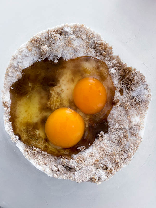 The eggs and sugars are in a glass bowl ready to be beaten together with a hand-held whisk.