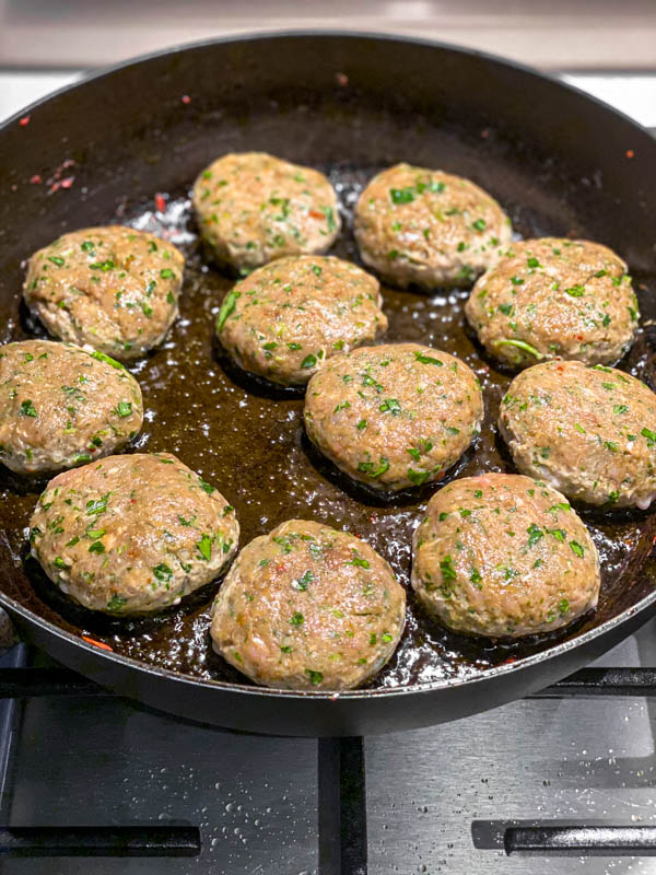 The Kofta patties are frying off in a pan.