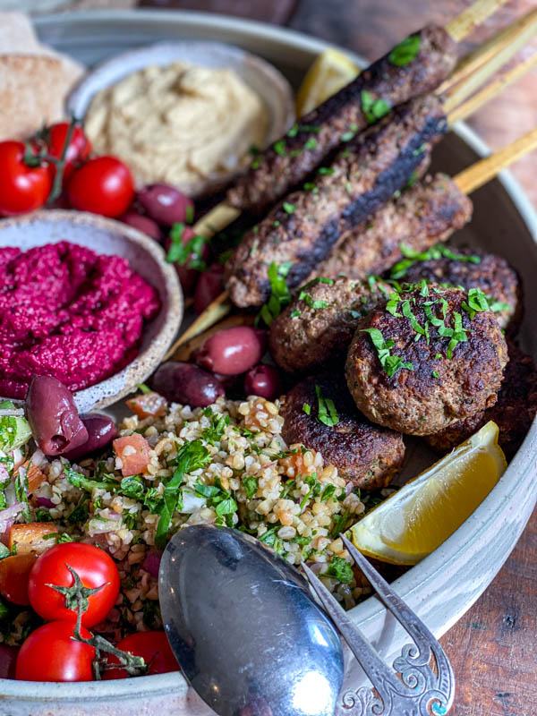 A close-up of the kofta skewers and patties that form part of a Middle Eastern style platter. There is also tabbouleh, olives, tomatoes and dips on the platter.