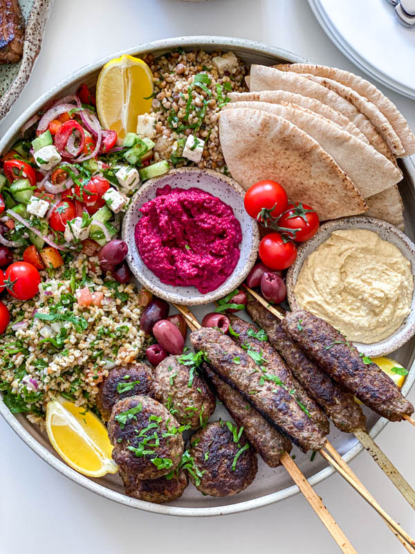 Looking down onto the Middle Eastern inspired platter featuring kofta skewers and patties. There is also pita bread triangles, hummus, beetroot dip, tabbouleh, greek salad, olives and tomatoes on the platter as well.