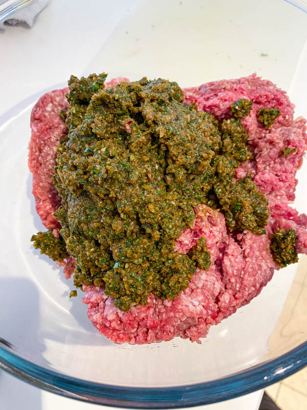 The herb and spice mix is added to the mince meat in a glass bowl.