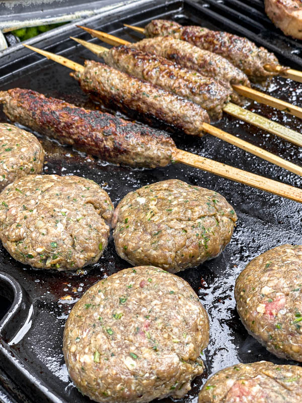 The kofta skewers and patties are cooking on a barbeque plate.